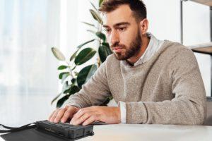 Image shows man using a Brailliant BI 20X on a desk